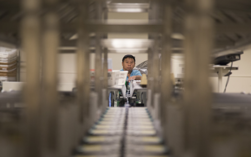 Photo originally published July 16 in Capitol Report and Politics in Minnesota. Machine operator Ningzhung B. Lee prepares to feed mail into an optical character-recognition scanning machine at the Minnesota Department of Administration's Mail Services office. The operation is housed inside the Department of Transportation building in St. Paul, Minn. Photo: Kevin Featherly.
