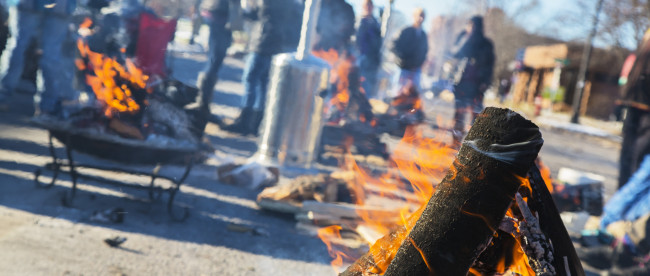 A wood fire burns in the street in front of the 4th Police Precinct, Minneapolis, Minn., as part of an ongoing protest following the police shooting of Jamar Clark. Photo: Kevin Featherly
